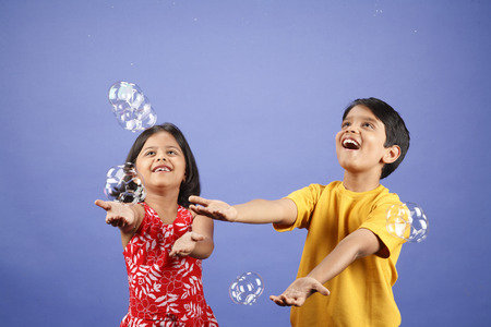 Ten and eight year old boy and eight year old girl playing with soap bubbles