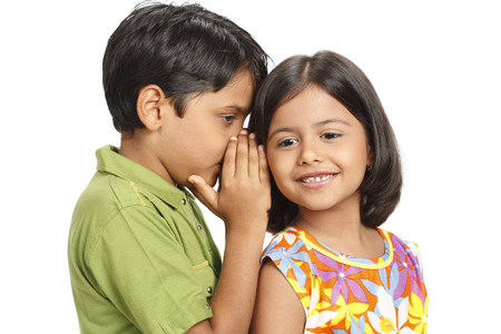 Ten year old boy whispering something in eight year old girls ear  Stock Photo