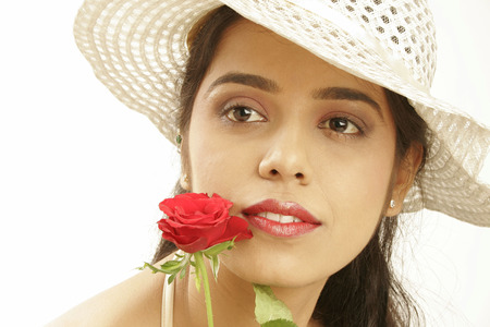 South Asian Indian teenage girl wearing beige hat holding red rose giving romantic and glamorous look