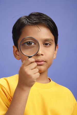 Ten year old boy looking through magnifying glass and both eyes open