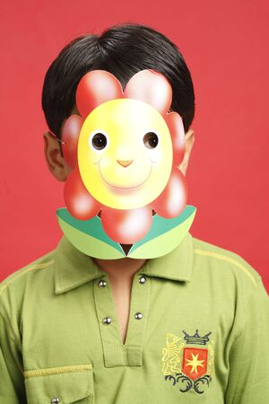 Ten year old boy wearing paper mask with flower printed on it Stock Photo
