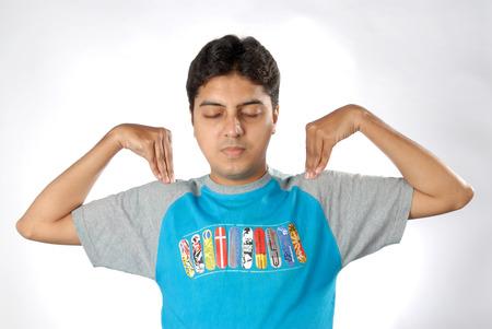 어깨에 양손을 유지하면서 눈을 감고 운동을하는 남 아시아 인디언 남자