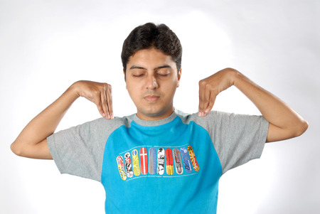 South Asian Indian man doing exercise closing eyes keeping both hand on shoulder