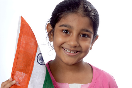 South Asian Indian eight year old girl holding flag of India looking at camera Stock Photo