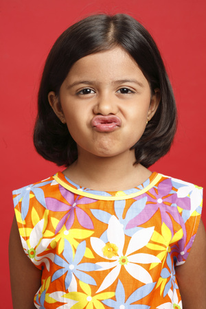 Eight year old girl making funny lips and face expression