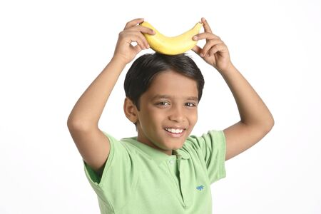 10 살짜리 소년이 양손으로 잡고있는 머리에 노란색 바나나를 보관했습니다. MR703V