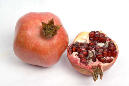 Fruits,one full and half red pomegranates on white background
