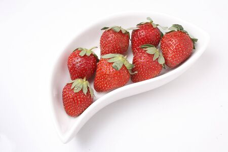 Fruit,Strawberry Fragaria Ananassa kept in s shaped serving tray on white background Stock Photo