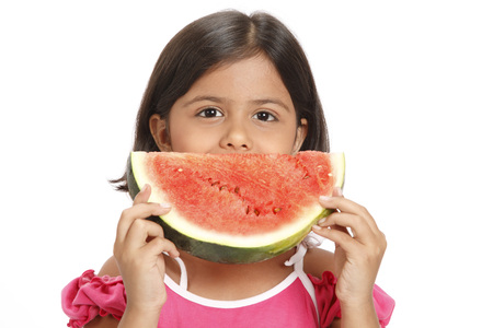 Eight year old girl holding half round watermelon slice in both hands near his mouth Stock Photo