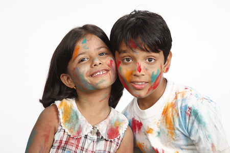 Ten and eight year old boy and girl posing with heads touched to each other on Holi festival