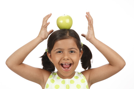 Eight year old girl kept green apple on head and balancing it Stock Photo