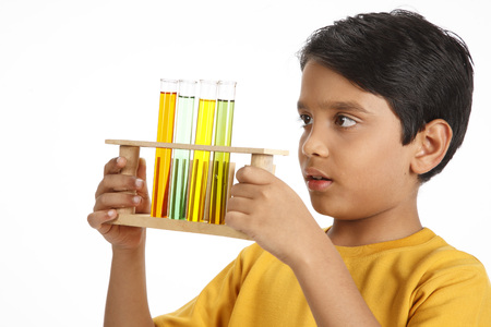 Ten year old boy holding test tubes filled with color water