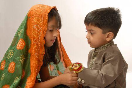 Girl tying rakhi on wrist of boy on Rakshabandhan festival