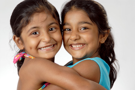South Asian Indian two girls hugging each other and smiling Stock Photo