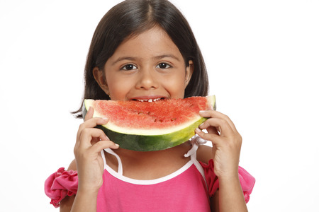 Eight year old girl holding half round watermelon slice and taking bite