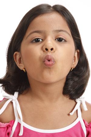 Eight year old girl making lips shape like kissing Stock Photo