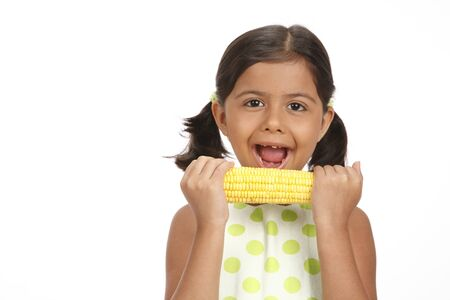 Eight year old girl holding sweet corn in both hands and trying to eat