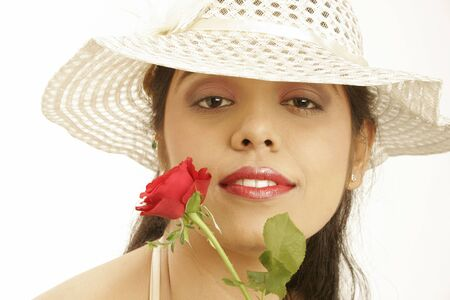 South Asian Indian teenage girl wearing beige hat holding red rose