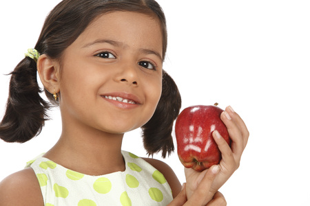 Eight year old girl holding red apple in one hand and thinking of eating