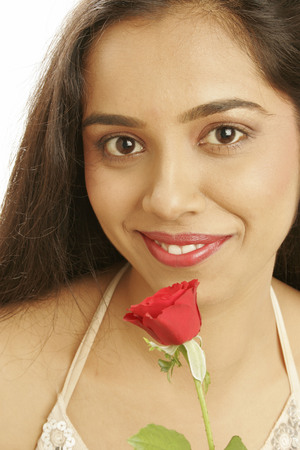 South Asian Indian teenage girl wearing beige halter top holding red rose