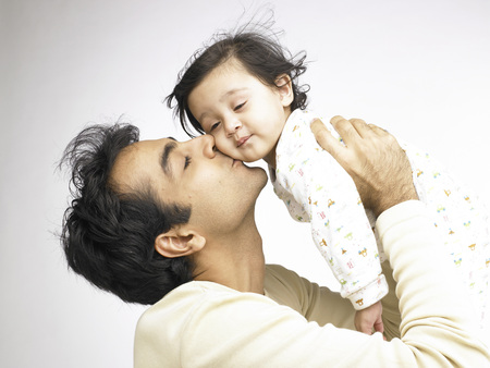Indian father kissing on cheek of baby girl