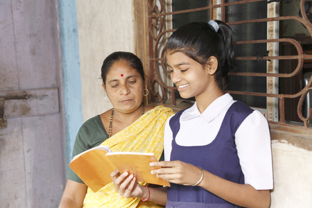 Mother sitting next to school going daughter reading book,Maharashtra,India Stock Photo