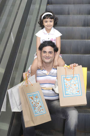 Father carrying daughter on shoulder holding bags sitting on escalator in shopping mall Stock Photo