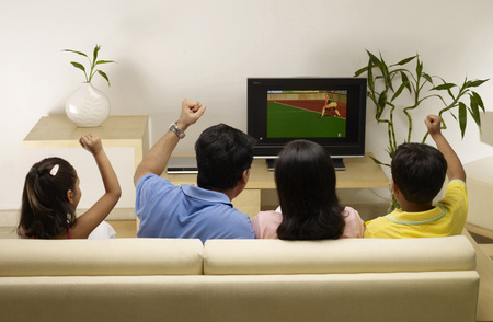 Children with parents cheering while watching match on TV sitting in house Stock Photo
