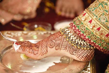 Vadhu pooja welcoming bride by washing her feet by milk in Indian Maharashtrian Hindu wedding Stock Photo