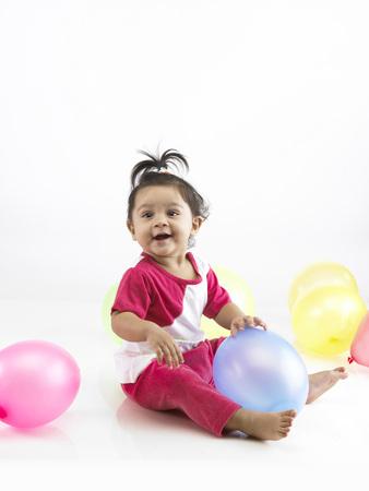 Joyful Indian baby girl wearing dress playing with balloon