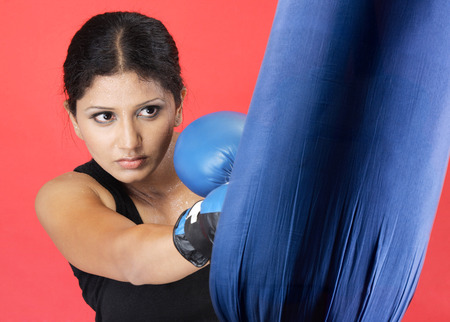 Female boxer in boxing outfit practicing on punching bag