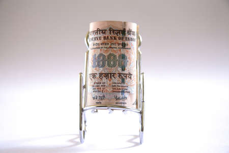 Concept,Indian currency one thousand rupees on relax stainless steel chair Stock Photo