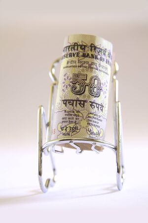 Concept,Indian currency fifty rupees on relax stainless steel chair