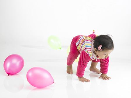 Indian baby girl wearing dress trying to stand up
