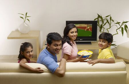 family sofa: Children with parents looking at camera sitting in house