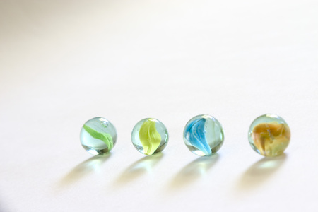 Four zero round glass marbles on white background Banque d'images