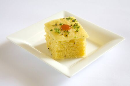 spongy: Indian cuisine,fast food Dhokla served with tomato ketchup in dish on white background