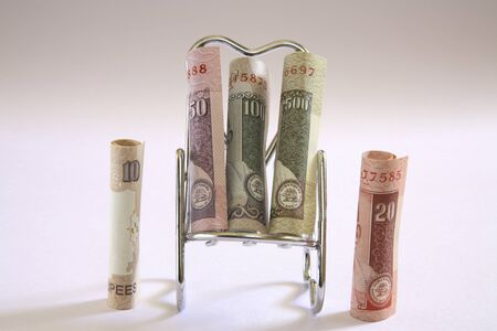 Concept,Indian currency ten twenty and fifty rupees and one hundred five hundred on relax stainless steel chair