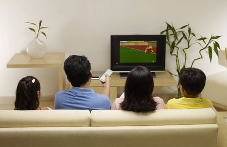 Children with parents watching match on TV sitting in house Stock Photo
