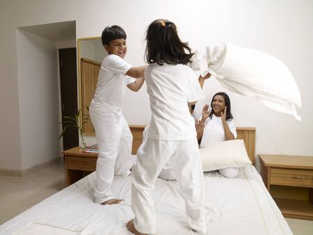 Children doing pillow fighting and parents watching them in bedroom