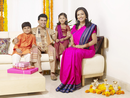family sofa: Parents with children in traditional wearing sitting in house