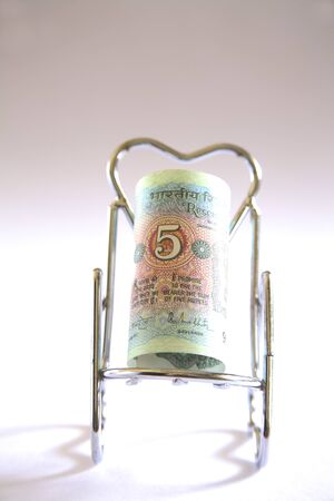 Concept,Indian currency five rupees on relax stainless steel chair