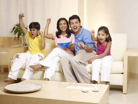 Children with parents cheering while watching TV sitting in house