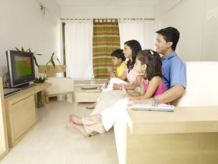 Children with parents watching TV sitting in house