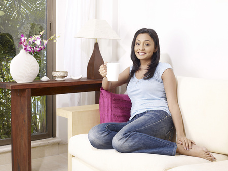 contemporary living room: Young lady showing white mug sitting on sofa