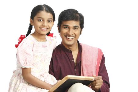 부유 한 인도 농부가 슬레이트를 딸에게 쓰는 법을 가르치고있다.