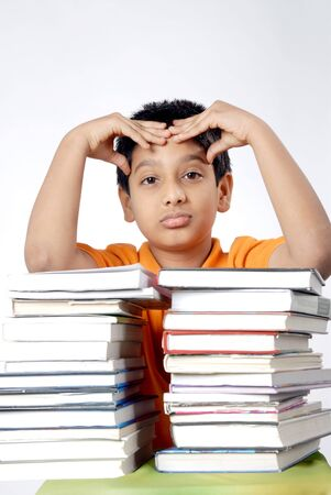 Boy in tension standing with stack of books