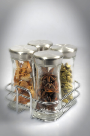 Four spices jar set with mace stae anise cardamom on white background Stock Photo