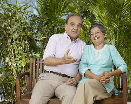 Old couple sitting on wooden bench Stock Photo
