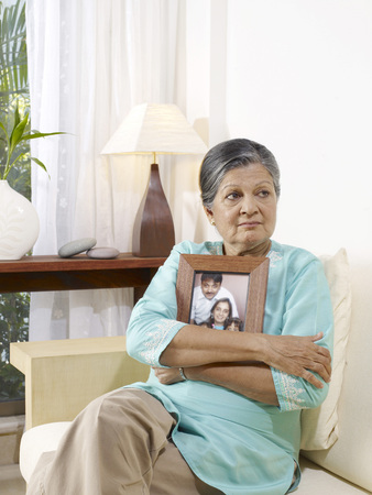 contemporary living room: Old lady in sad mood holding photo frame of family